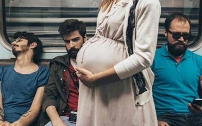беременная девушка стоит и ей не уступают место