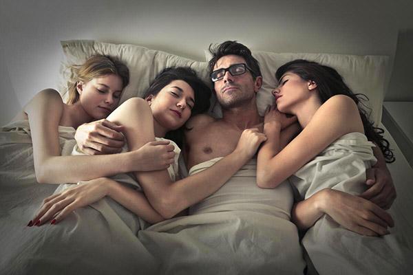 мужчина в постели с тремя женщинами